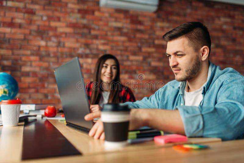 Universitaire studenten die bij de lijst samen bestuderen royalty-vrije stock afbeelding