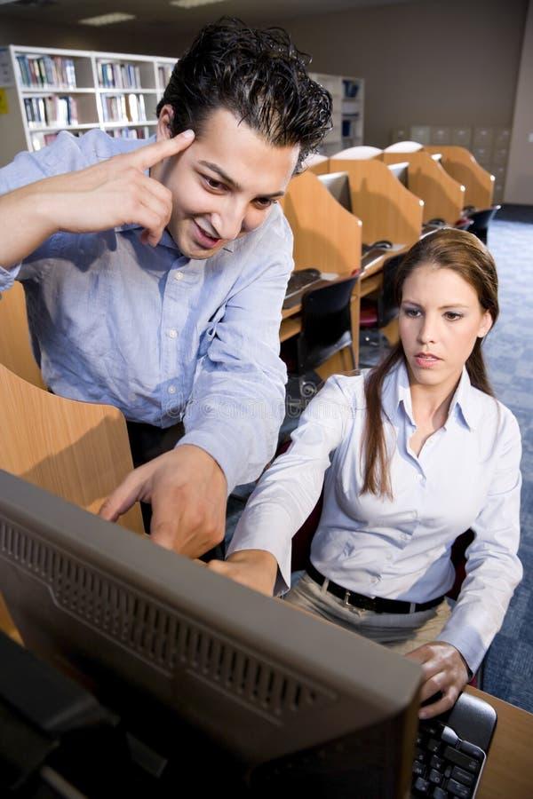 Universitaire studenten die computer in bibliotheek met behulp van stock foto's