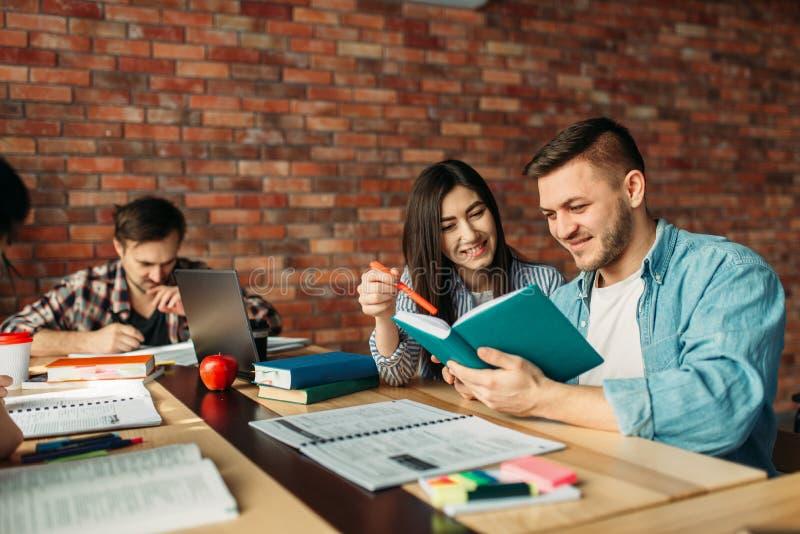 Universitaire studenten die handboek samen lezen stock afbeelding