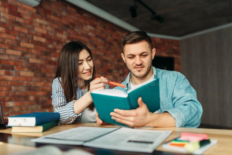 Universitaire studenten die handboek samen lezen stock foto
