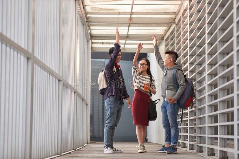 Universitaire Studenten die Hoogte Vijf geven stock fotografie