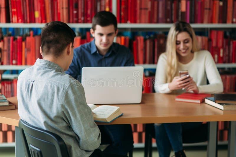 Universitaire studenten die samen bij de lijst met boeken en laptop zitten Gelukkige jongeren die groepsstudie in bibliotheek doe royalty-vrije stock foto's