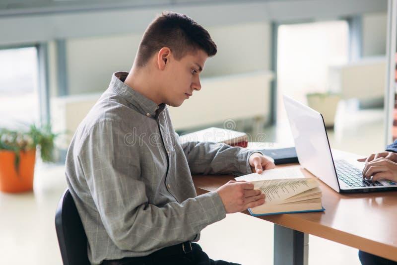 Universitaire studenten die samen bij de lijst met boeken en laptop zitten Gelukkige jongeren die groepsstudie in bibliotheek doe royalty-vrije stock afbeeldingen