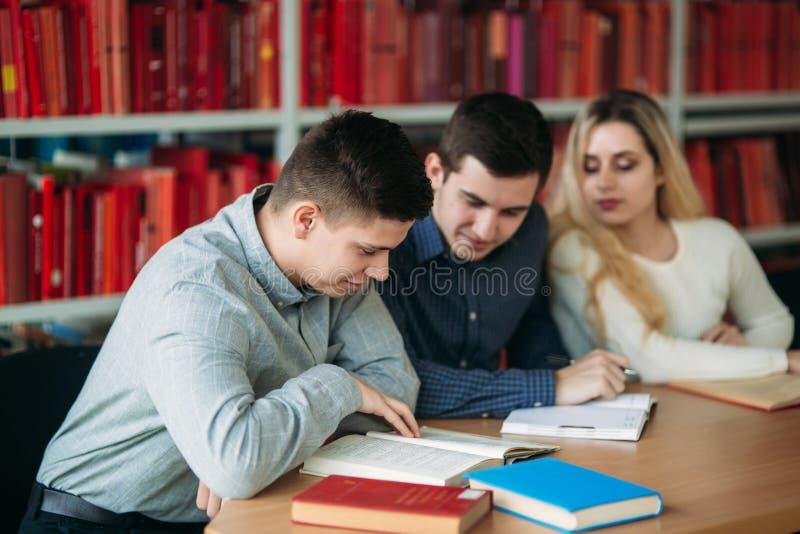 Universitaire studenten die samen bij de lijst met boeken en laptop zitten Gelukkige jongeren die groepsstudie in bibliotheek doe stock fotografie