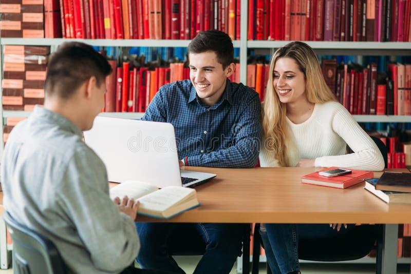Universitaire studenten die samen bij lijst met boeken en laptop zitten Gelukkige jongeren die groepsstudie in bibliotheek doen stock afbeeldingen