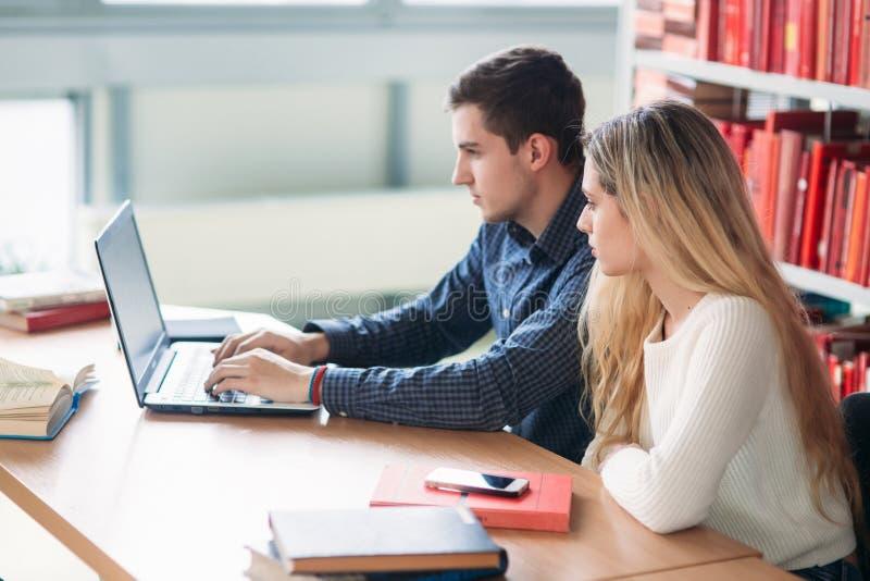 Universitaire studenten die samen bij lijst met boeken en laptop zitten Gelukkige jongeren die groepsstudie in bibliotheek doen royalty-vrije stock foto's