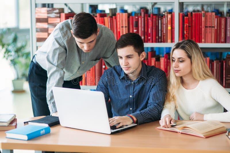Universitaire studenten die samen bij lijst met boeken en laptop zitten Gelukkige jongeren die groepsstudie in bibliotheek doen stock foto's