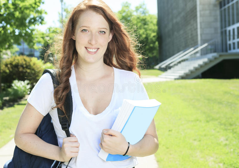 Universiteit/studentmeisje die gelukkig kijken stock foto