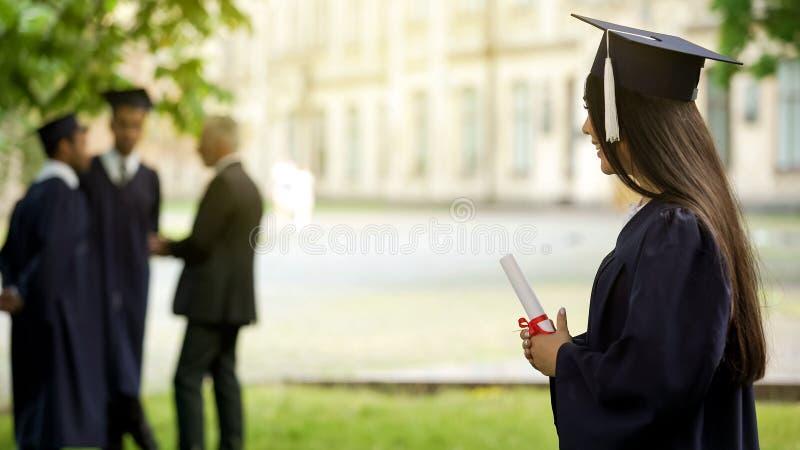 Universiteits vrouwelijke gediplomeerde die succesvolle voltooiing van onderwijs, toekomst vieren stock fotografie