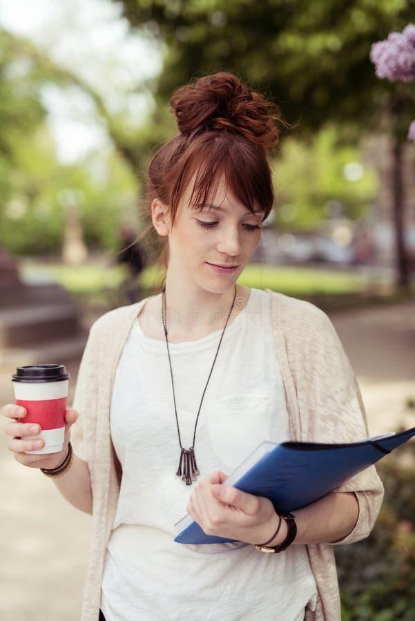 Universiteitsmeisje die een Koffie houden terwijl het Lezen van een Boek royalty-vrije stock fotografie