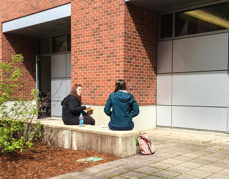 Universiteitsvrienden die bij openluchtlunch op een de lentedag spreken royalty-vrije stock afbeeldingen