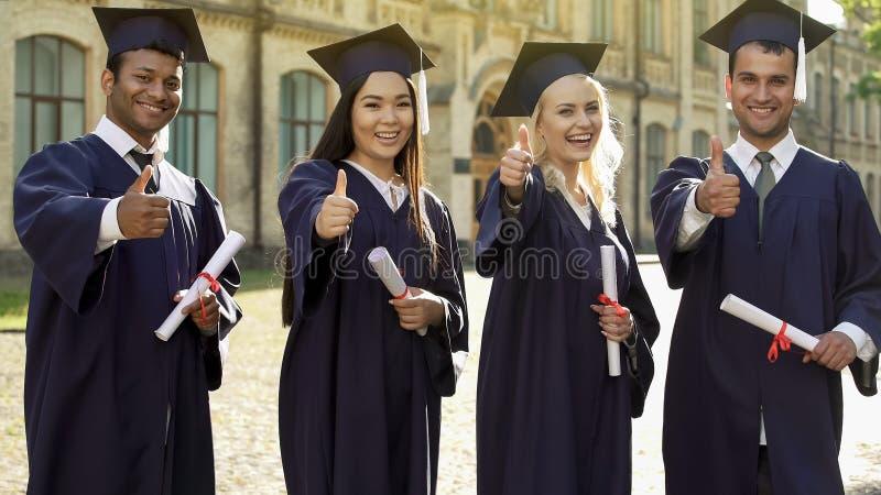Universitetkandidater i den akademiska regaliern som rymmer diplom som visar tummar-upp royaltyfri bild