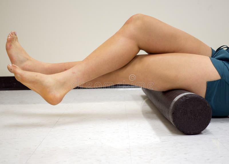 Universitets- idrottsman nen som använder en skumrulle för att släppa hennes åtsittande muskler arkivbild