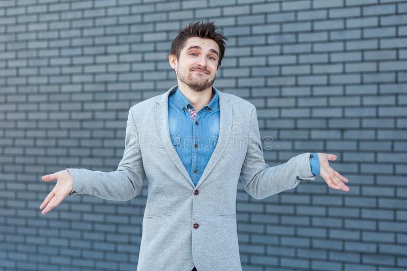 universitetsläraren vet jag t Stående av den förvirrade stiliga skäggiga mannen, i anseende för tillfällig stil, lyftta armar och arkivbilder