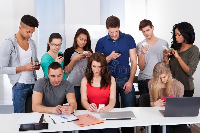 Universitetsstudenter som använder mobiltelefoner royaltyfri foto