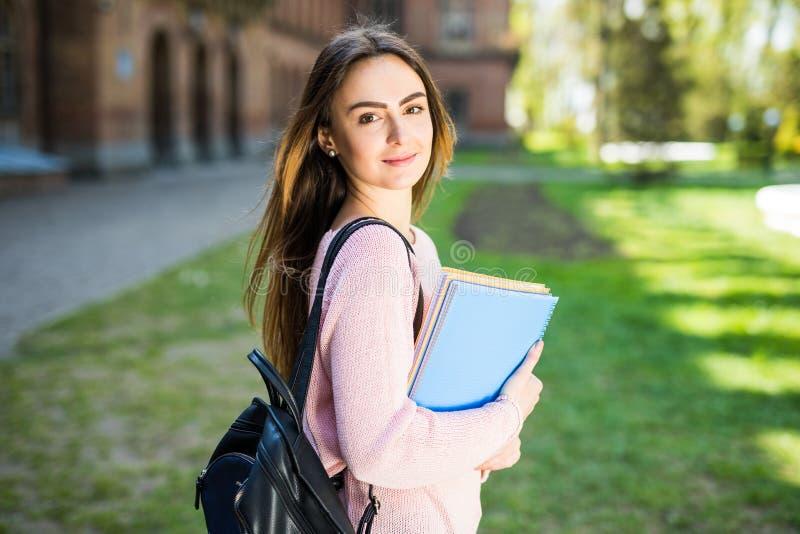 Universitetsstudentflickan som ser lyckligt le med boken, eller anteckningsboken i universitetsområde parkerar royaltyfria foton