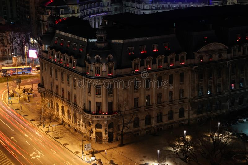 University of Bucharest during Earth Hour, candles in windows. University of Bucharest during Earth Hour, power off, candles lit by students in windows, night royalty free stock photo