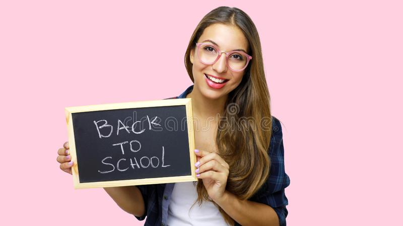 University college student showing blackboard saying back to school. Beautiful young female model isolated on pink background stock image