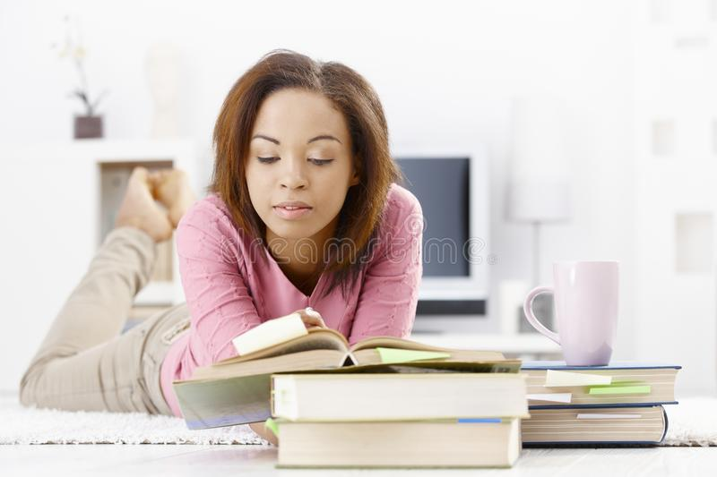 University girl studying at home. Reading book, lying on floor royalty free stock image