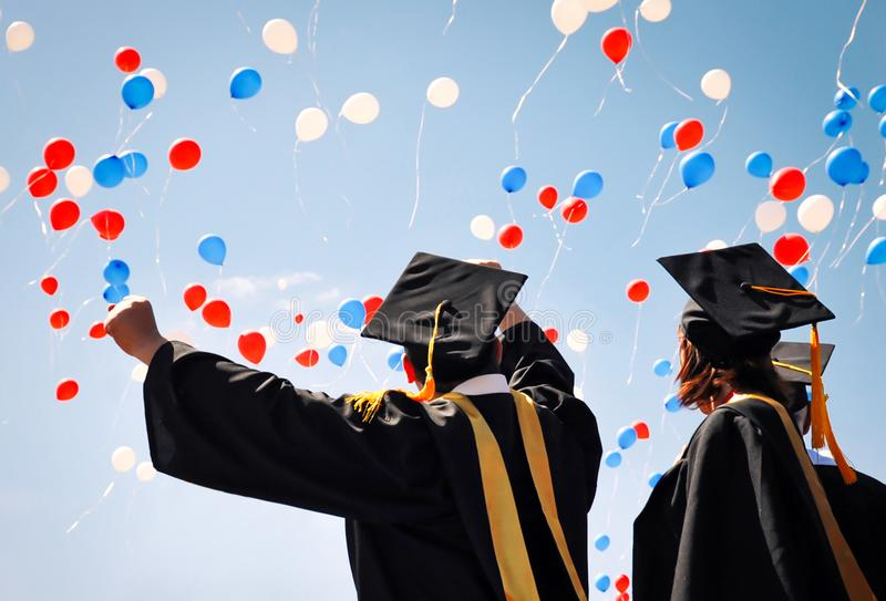 University graduates in black robes rejoice, raise their hands up against the sky and balloons stock image