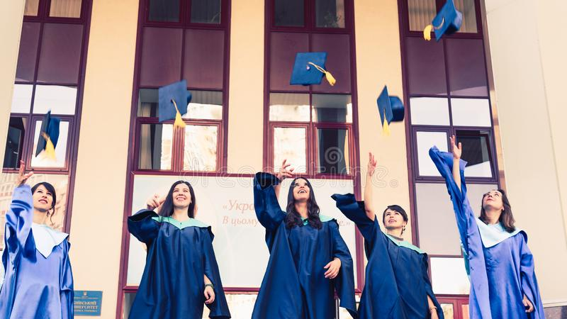 University graduates  throwing graduation hats in the air. Group of happy graduates in academic dresses near university building royalty free stock photos