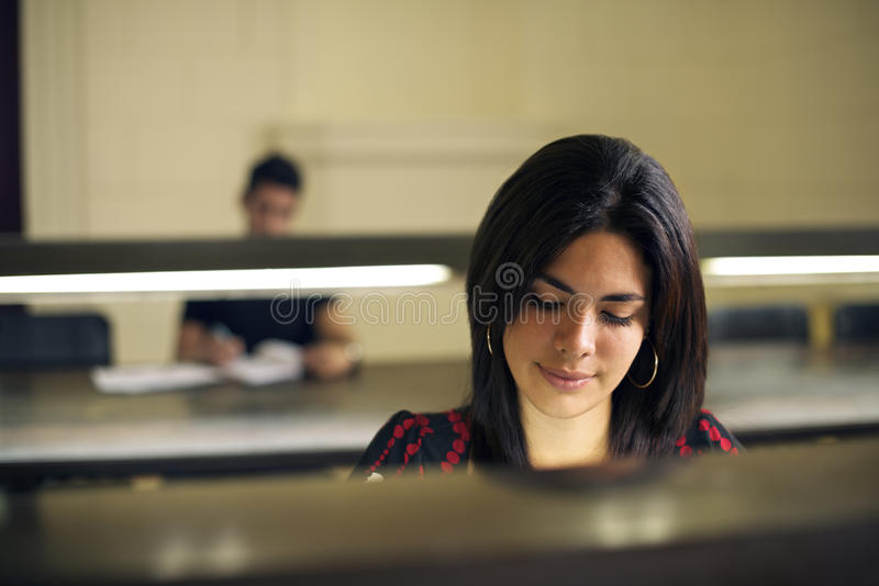 University library and female student, beautiful young woman stu. University library and female student, beautiful young women studying and preparing test in royalty free stock photos