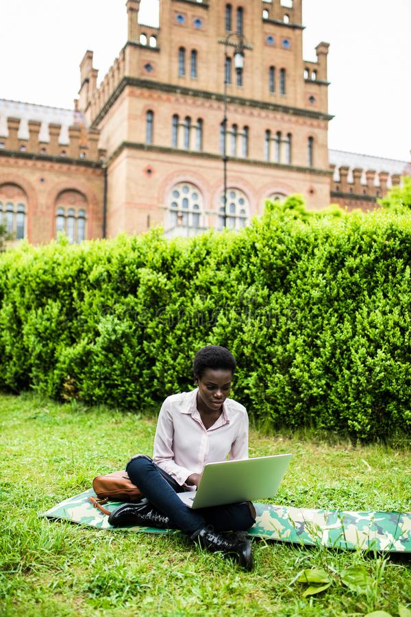 University life. Young student female african american woman enjoying a sunny day at the campus, working on laptop. Young female african american woman enjoying stock photos