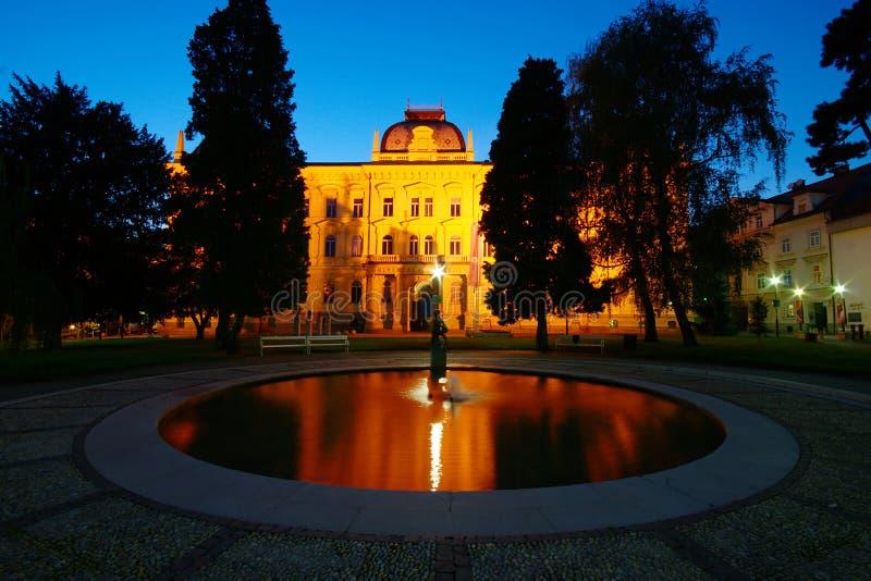 University Of Maribor, Slovenia. University Of Maribor and fountain on Slomsek Square by night stock photo