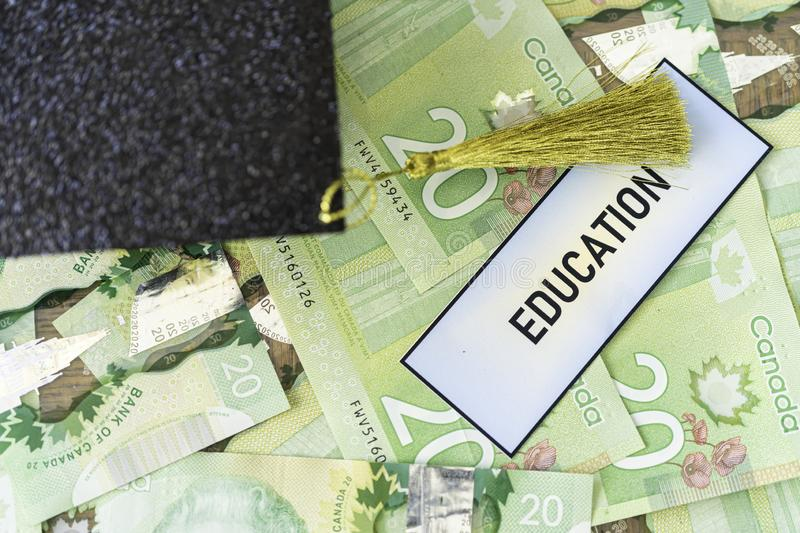 University Mortarboard academic cap on Canadian Dollar notes stock images