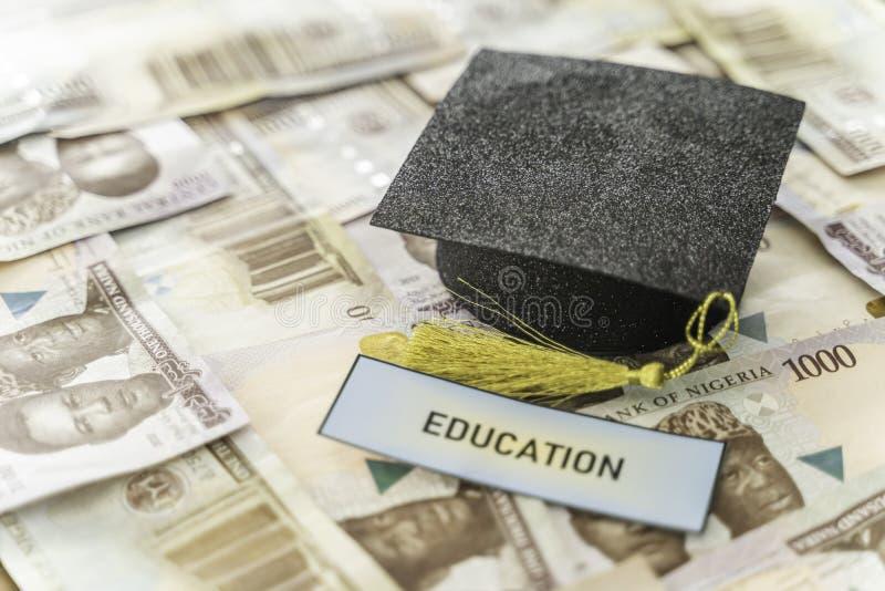 University Mortarboard academic cap on Nigerian Naira notes stock images