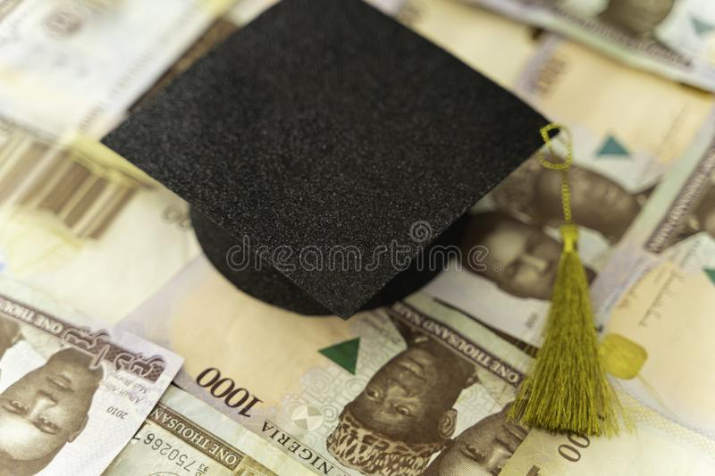 University Mortarboard academic cap on Nigerian Naira notes stock photos