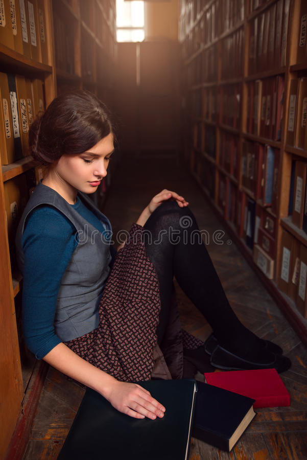 University student sitting on a floor of library. University student sitting on a floor of library with the spread out books and textbooks stock photos