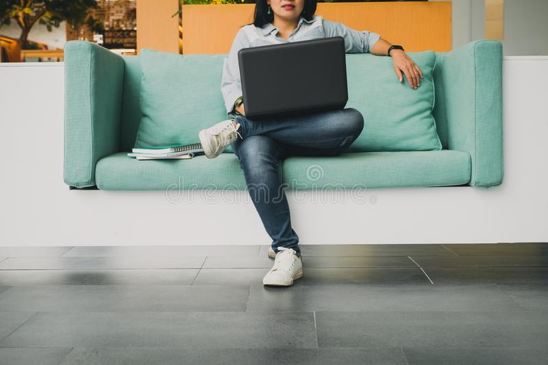 University student sitting in sofa and using laptop computer to. Study a lesson online,E-learning concept stock photography