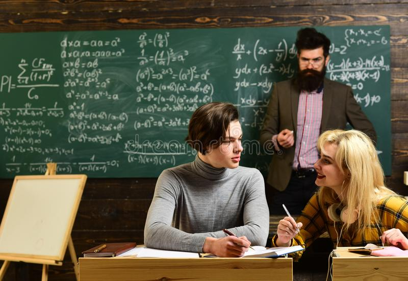 University students doing group study. Teenage female student preparing for exams at college classroom. Old books on a stock photography