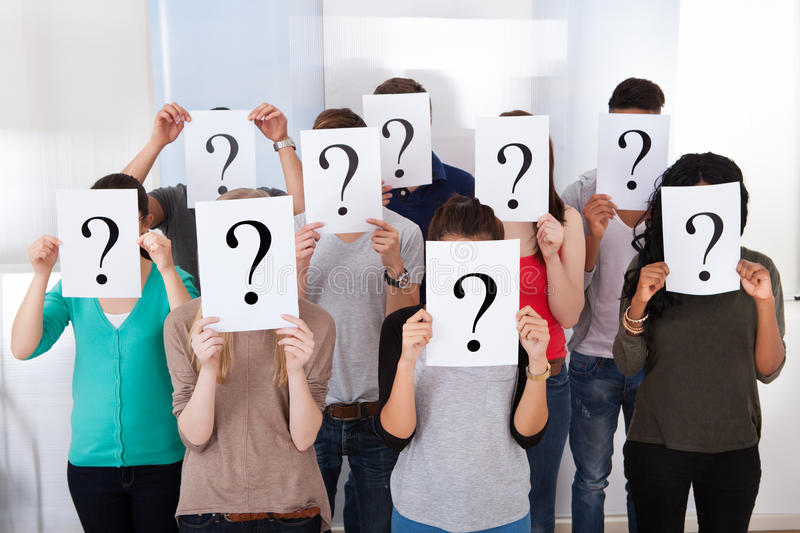 University students holding question mark signs. Group multiethnic university students holding question mark signs in front of their faces stock photo