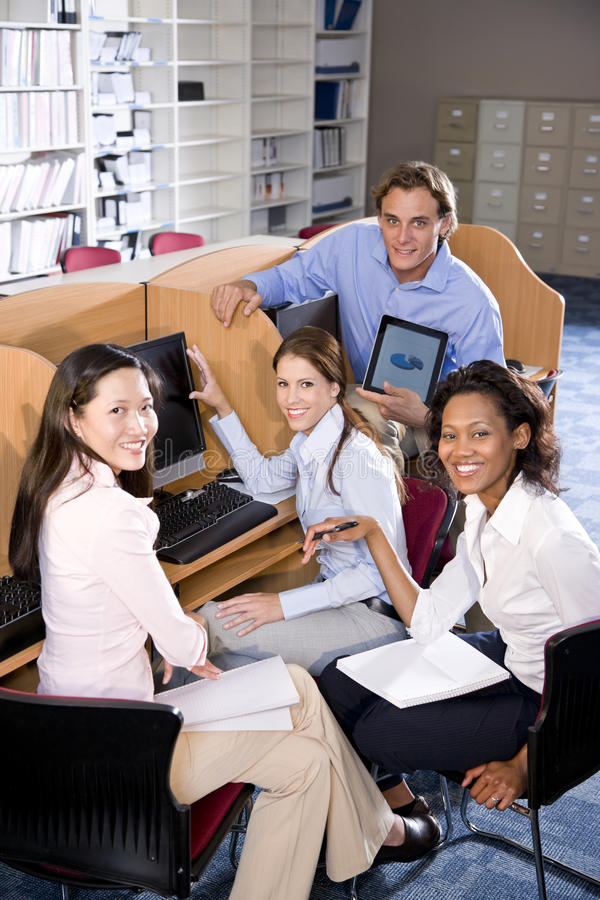 University students at library computer studying. Diverse university students at library computer studying stock photo