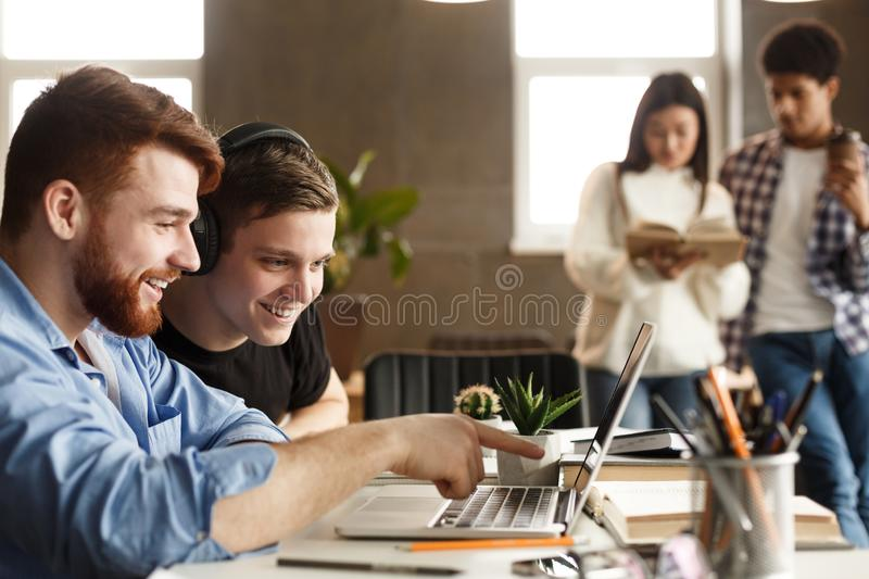 University students at library studying together and connecting online royalty free stock photography