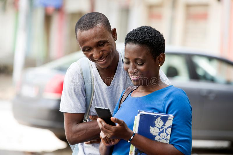 University students reading a message on a smart phone. Two young happy college students standing in the street are watching and reading a message on a smart stock photography