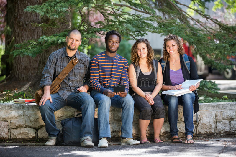 Download University Students Sitting On Parapet At Campus Stock Photo - Image: 37131562