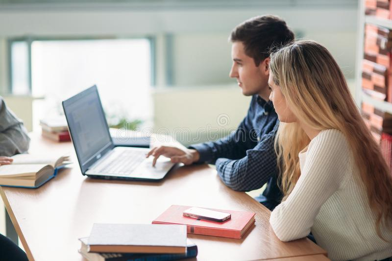 University students sitting together at table with books and laptop. Happy young people doing group study in library.  royalty free stock photography