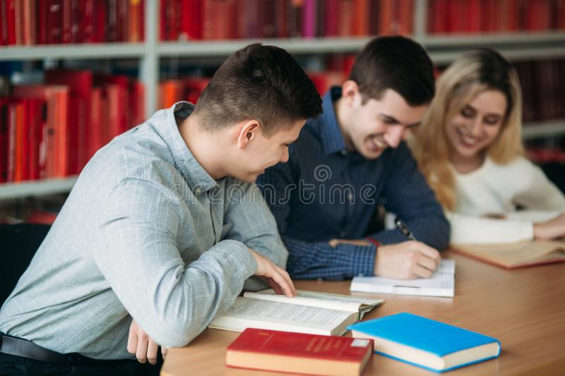 University students sitting together at table with books and laptop. Happy young people doing group study in library.  stock photo