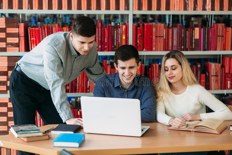 University students sitting together at table with books and laptop. Happy young people doing group study in library royalty free stock photography