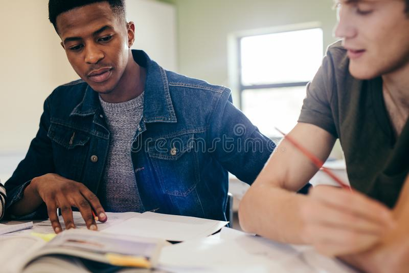 University students studying with books in library. Classmates sitting at a table and reading reference books for their project stock photos