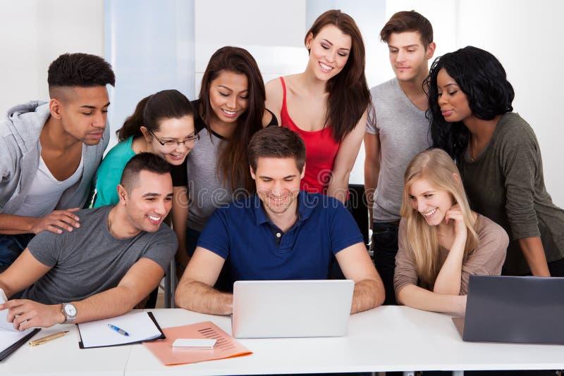University students using laptop together stock photography