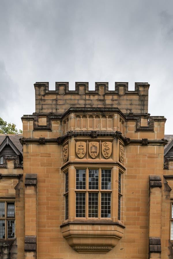 University of Sydney Quadrangle facade part, Australia. Sydney, Australia - March 25, 2017: Brown stone balcony and series of emblems in quadrangle of stock photo