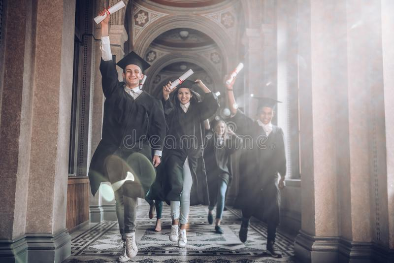 University was the best years of their lives!Group of smiling university students holding their diplomas and running after being stock photo