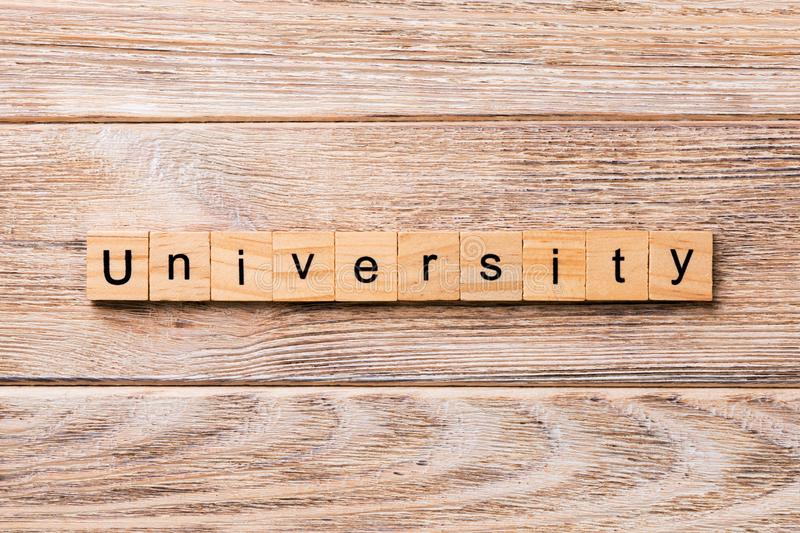 UNIVERSITY word written on wood block. UNIVERSITY text on wooden table for your desing, concept royalty free stock photography
