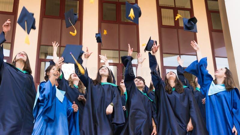 Uniwersytet kończy studia miotania skalowania kapelusze w powietrzu Grupa szczęśliwi absolwenci w naukowu ubiera blisko uniwersyt obrazy royalty free
