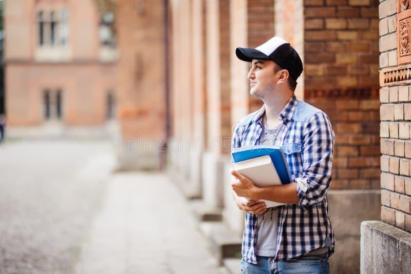uniwersytet Uśmiechnięty młody studencki mężczyzna trzyma książkę i torbę na uniwersyteckim tle Młody uśmiechnięty ucznia życia s zdjęcia stock