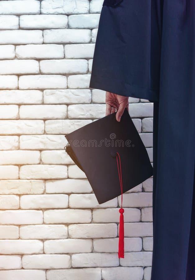 Uniwersyteta absolwent trzymał jego kapelusz dumnie obraz royalty free